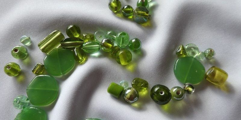 Pourquoi un blog illustré par des perles vertes sur du tissu blanc.