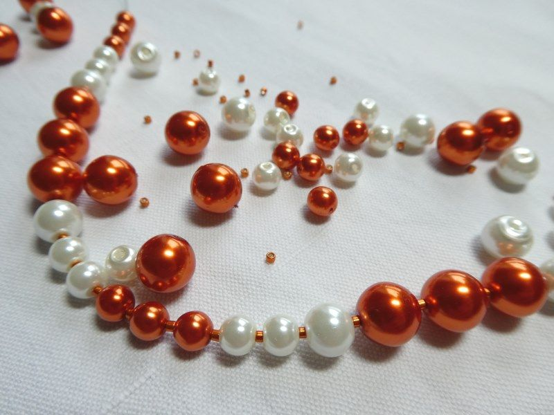 Grand collier en cours de réalisation avec des perles oranges et blanches.