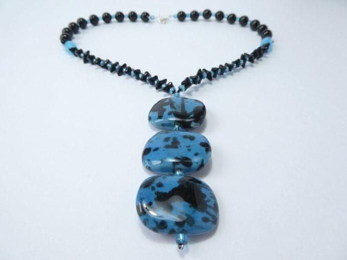 Un collier avec pendentif composé de trois perles plates.