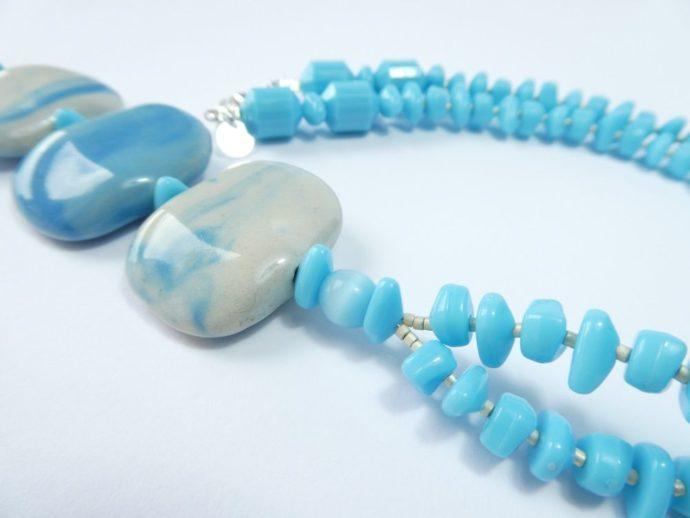Détail du collier bleu ciel avec pendentif.