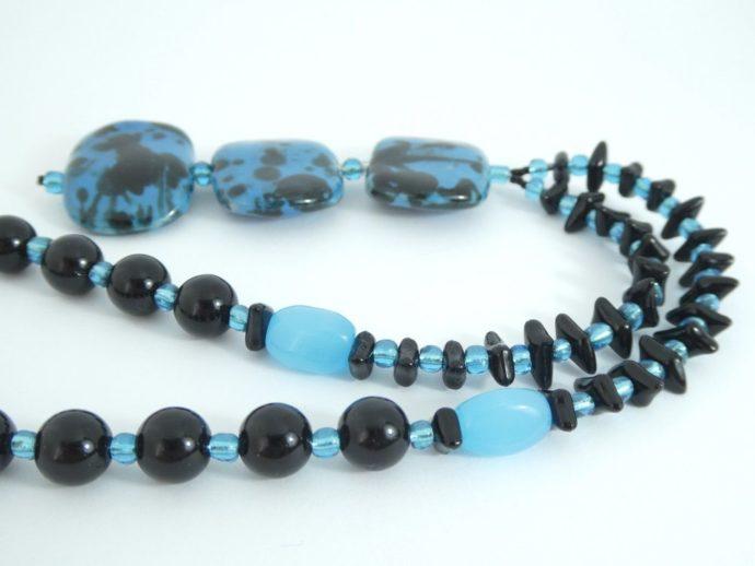 Détail du collier avec pendentif noir et bleu.
