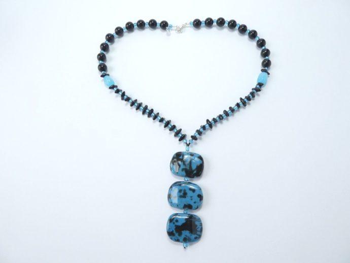 Collier avec pendentif noir et bleu.