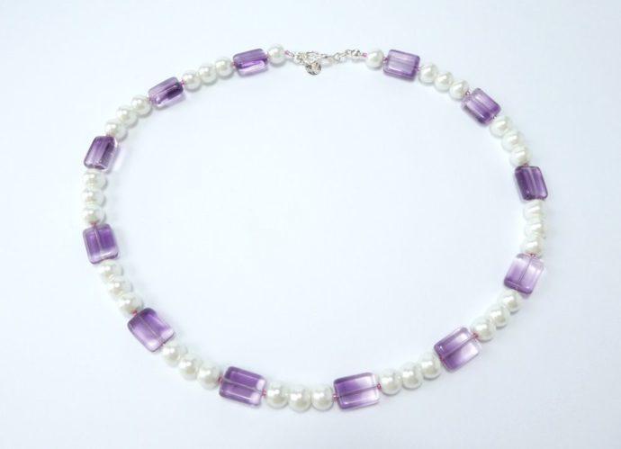 Collier composé de perles rondes blanches et rectangulaires mauves.