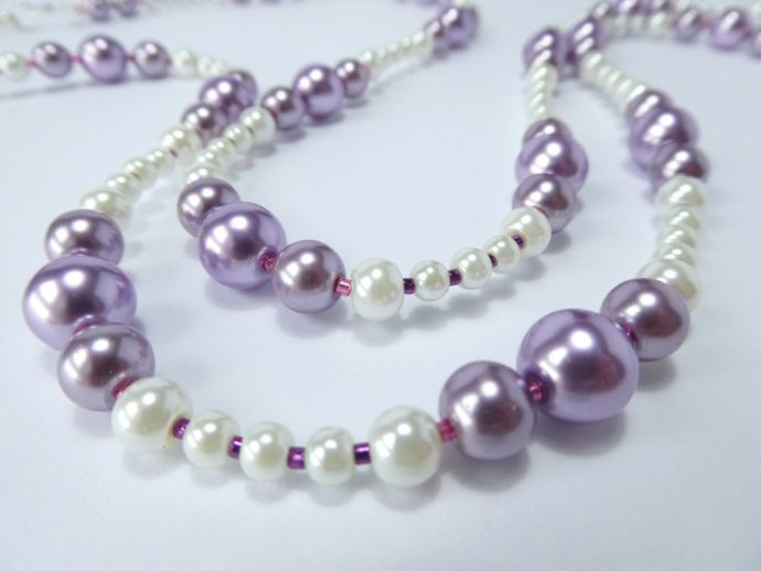 Détail des perles du sautoir mauve et blanc.