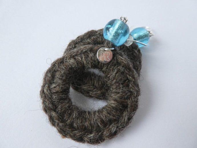 Boucles d'oreilles en laine avec perle bleue.