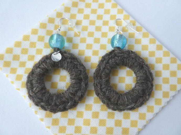 Boucles d'oreilles en laine posées sur la lingette d'entretien.