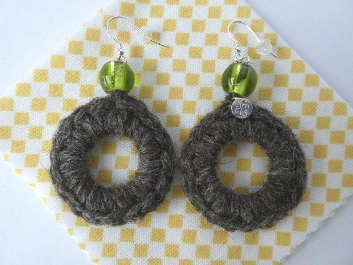 Boucles d'oreilles avec laine et perle verte et la lingette d'entretien.