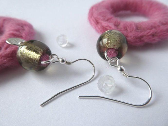 Détail des crochets d'oreilles en laine rose.