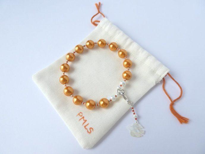 Bracelet orange et son sachet de protection.
