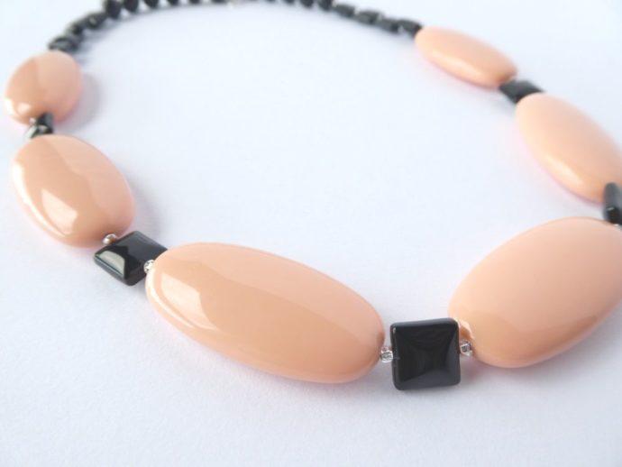 Les perles carrées et plates noires du collier art déco rose poudré.
