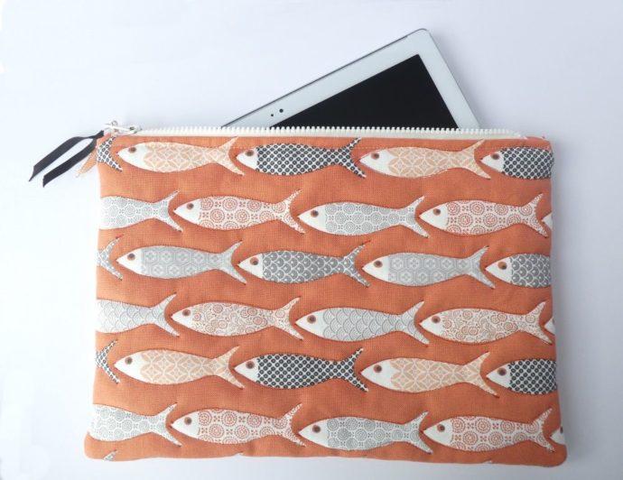 La pochette matelassée de couleur corail avec motif poisson.