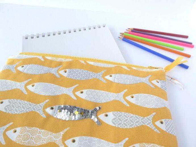 La pochette jaune motif poisson et des crayons.