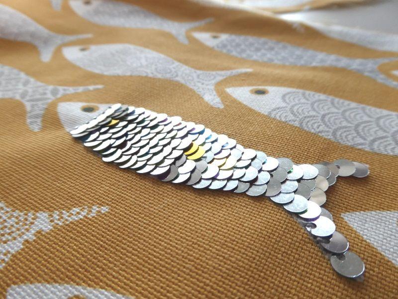 Sequins brodés sur un motif poisson de la pochette jaune.
