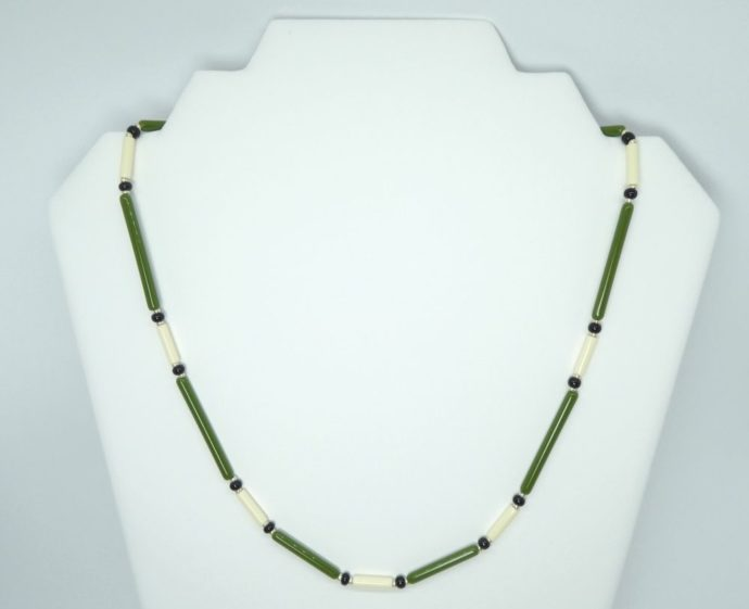 Présentation du collier vert ivoire avec ces perles en forme de tube.