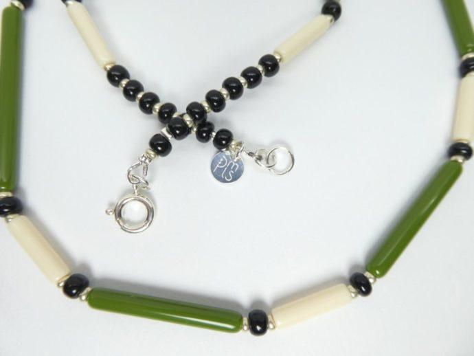 Gros plan sur le fermoir et la marque PMLS du collier vert et ivoire.