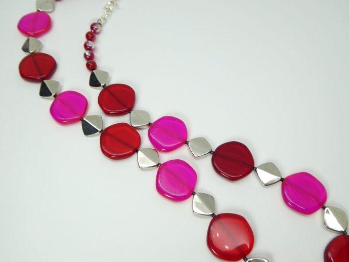 Les perles rouges et rose fluo séparées par des perles métalliques.