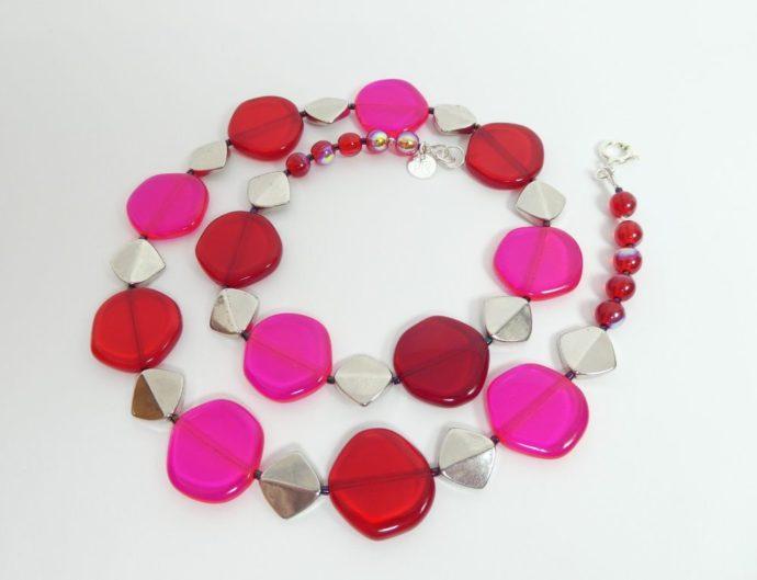 Le collier rouge et rose fluo a aussi des perles métalliques.