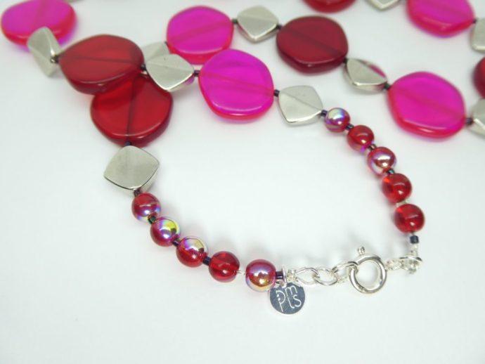 Détail du fermoir du collier rouge et rose fluo.