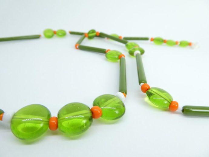 Gros plan du long collier vert et orange avec perles de forme tube et rondes translucides.