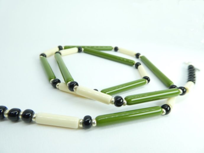 Perles noires du collier vert et ivoire.