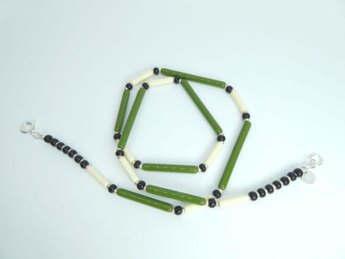 Les perles en forme de tube du collier vert et ivoire.