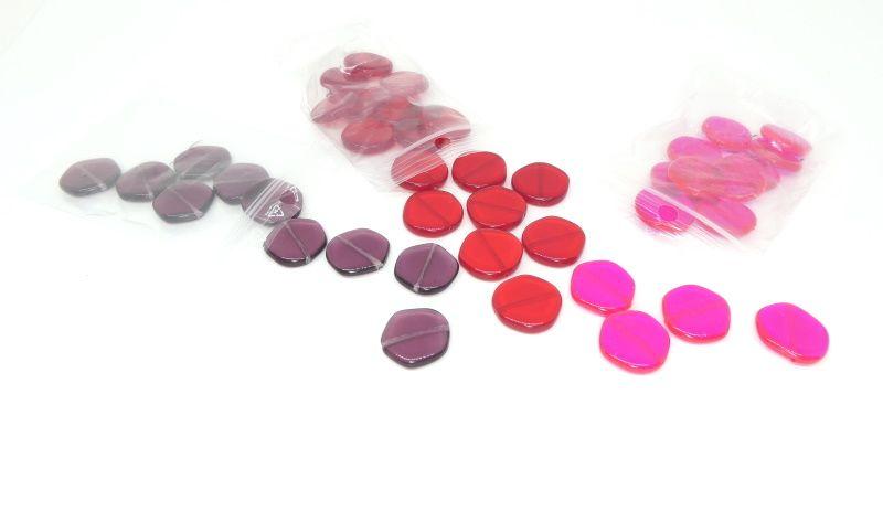 Des perles en forme de palets plats mauves, rouges et rose fluo.