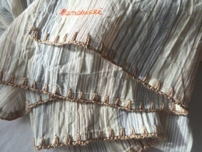 Finition crochetée couleur caramel pour l'écharpe à rayures bleues.