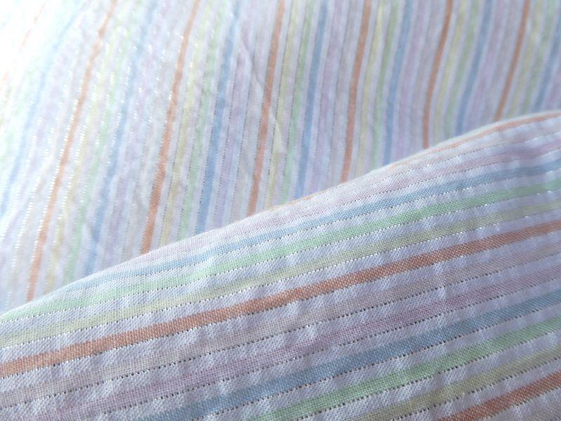 Le tissu à rayures pastel et fil Lurex pour l'écharpe.