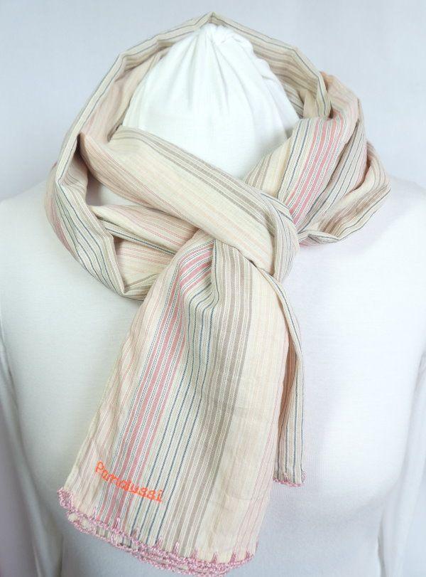 L'écharpe en tissu à rayures roses avec finition crochetée rose.