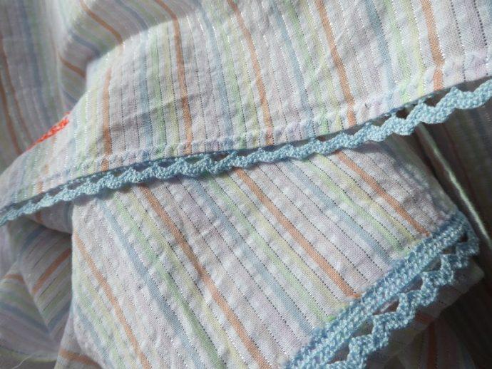 Le feston bleu qui borde l'écharpe à rayures pastel.
