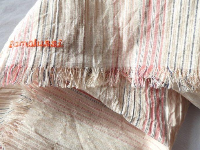 Les franges de l'écharpe en tissu à rayures roses.