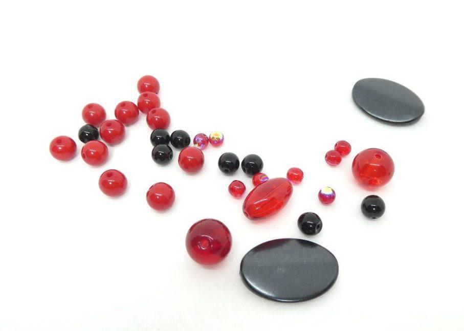 Des perles rouges rencontrent des perles noires dans l'atelier Pamalussi.