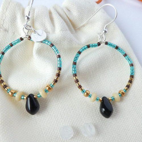 Boucles d'oreilles bleu sarcelle avec un pendant en forme de goutte noire.