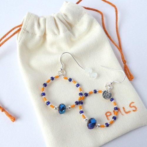 Les boucles d'oreilles bleues et orange sur leur pochon en flanelle.