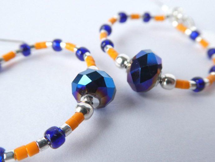 Les perles à facettes en cristal des boucles d'oreilles bleues et orange.