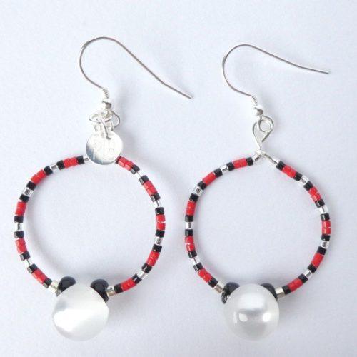 Les boucles d'oreilles blanc nacré, rouges et noires ont une perle bouton.