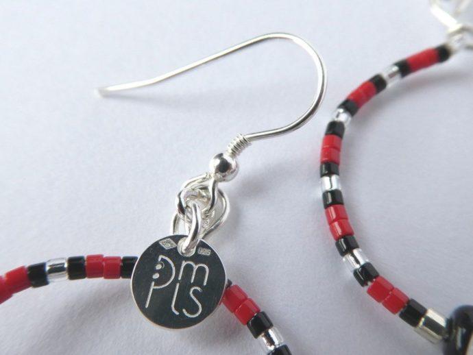 Le crochet des boucles d'oreilles blanc nacré, rouges et noires.