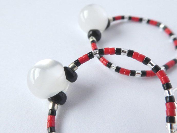 La perle bouton des boucles d'oreilles blanc nacré, rouges et noires.
