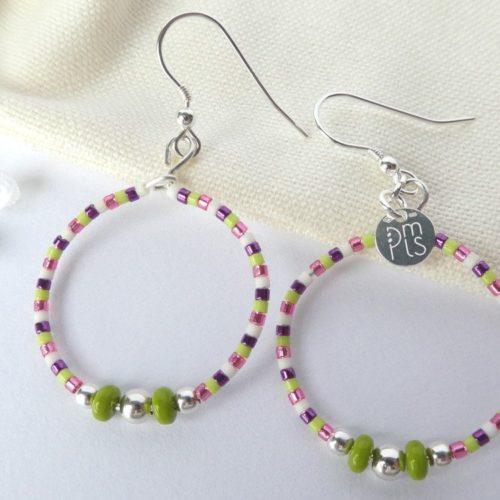 Boucles d'oreilles vertes et roses sur leur pochon en flanelle.