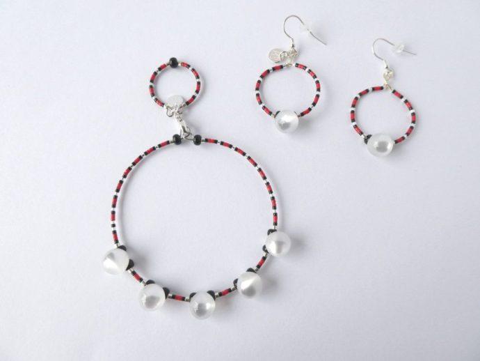 Le bracelet blanc nacré rouge et noir et les boucles d'oreilles assorties.