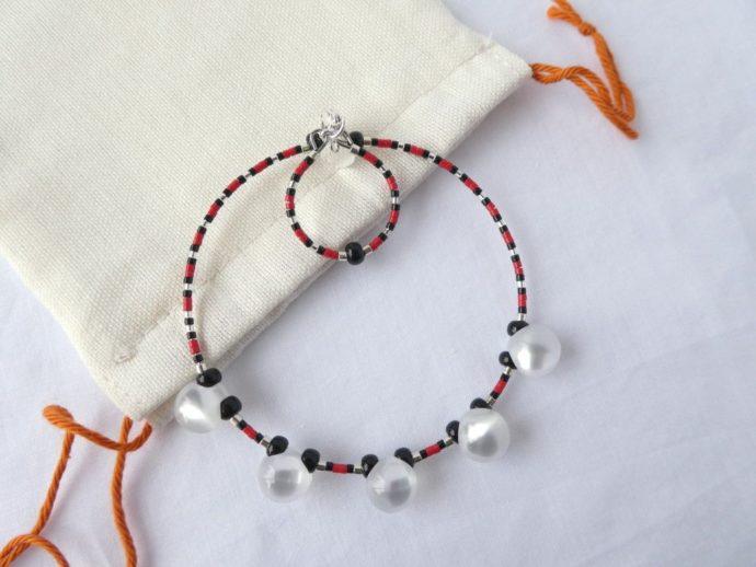 Le bracelet blanc nacré, rouge et noir et son pochon en coton.