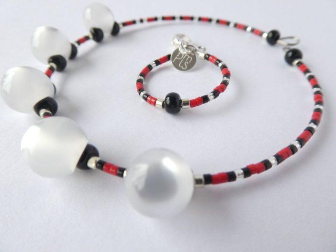 Gros plan sur les perles du bracelet blanc nacré rouge et noir.