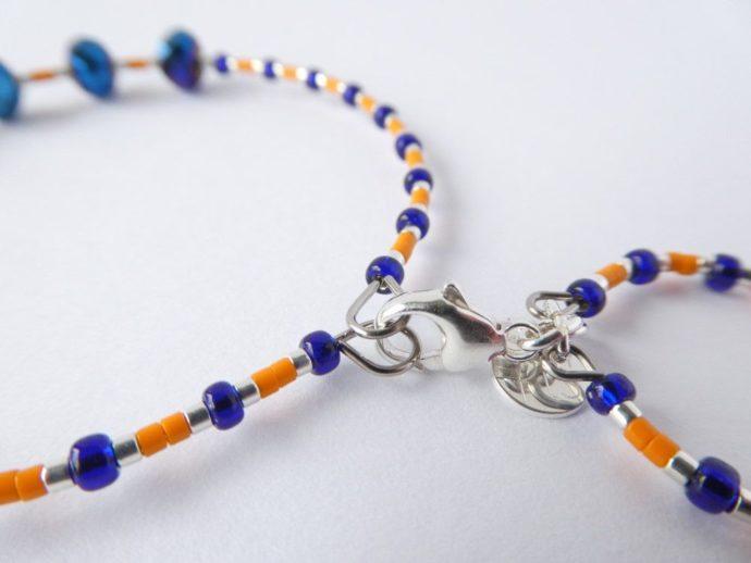 Détail du fermoir du bracelet bleu et orange.