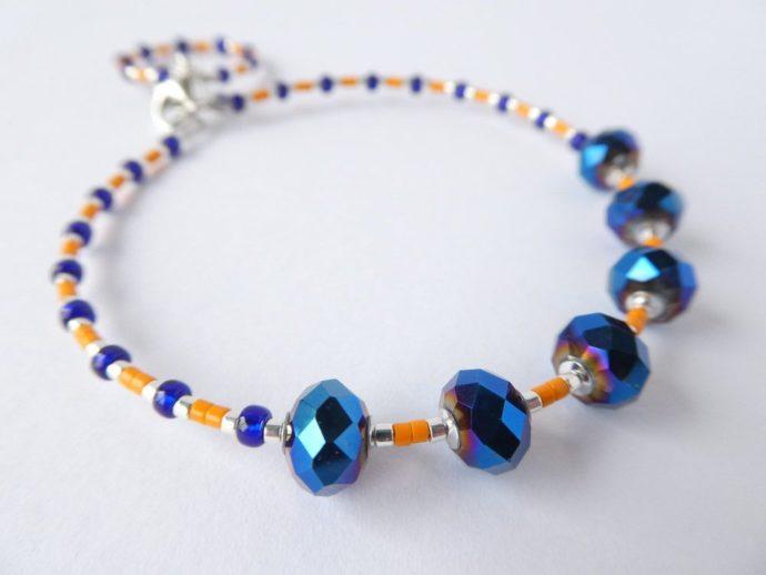 Les perles à facettes bleu nuit du bracelet bleu et orange.