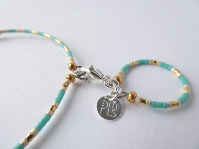Le fermoir et la marque PMLS du bracelet vert d'eau.