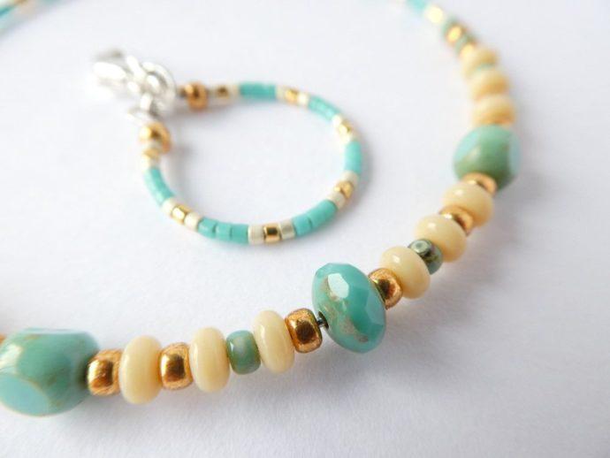 Un gros plan sur les perles du bracelet vert d'eau.