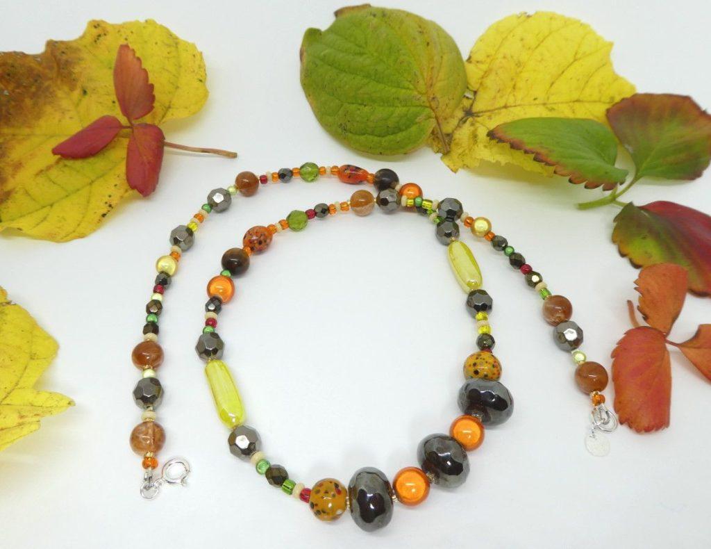 Collier aux couleurs de l'automne entouré de feuilles.