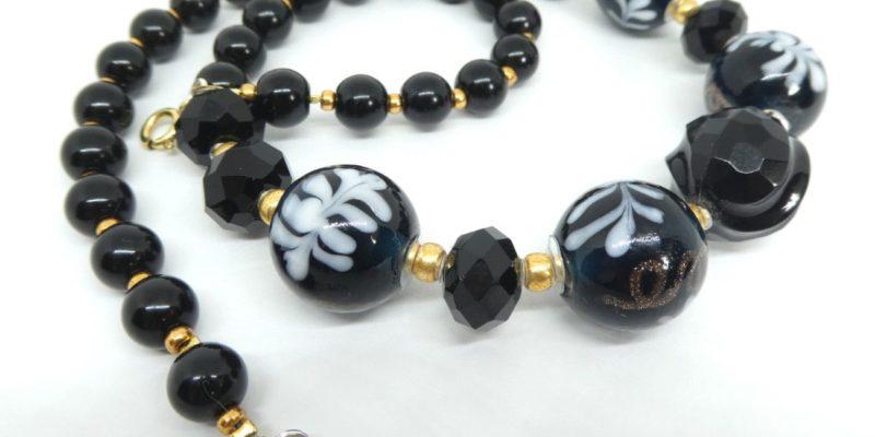 Gros plan sur les perles noires et blanches du collier noir et or.