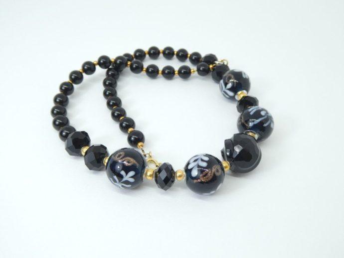 Les perles rondes en verre du collier noir et or.