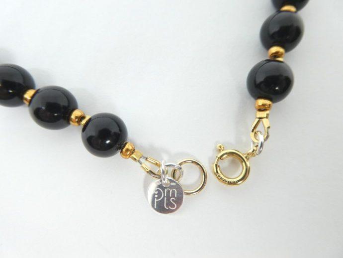 Le fermoir en Gold filled 14 k du collier noir et or.